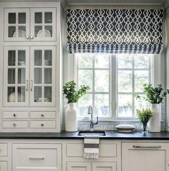 Dark floors and countertops, and white cabinets. Modern blinds in the  kitchen